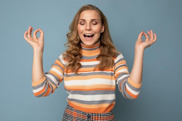 Porträt einer positiven glücklichen jungen attraktiven blonden lockigen frau mit aufrichtigen emotionen, die trendy trägt