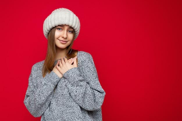 Porträt einer positiven glücklichen jungen schönen dunkelblonden frau mit aufrichtigen gefühlen, die grau trägt