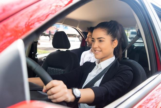 Porträt einer professionellen fahrerin, die ihr auto fährt. transportkonzept.
