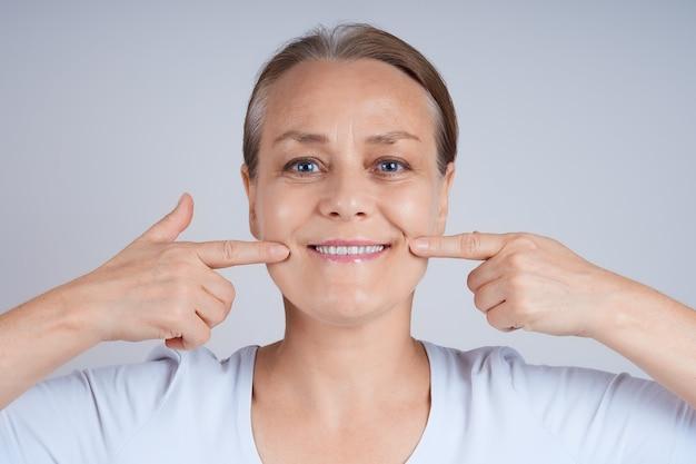 Porträt einer reifen frau in einem weißen t-shirt, das ihr gesicht mit ihren fingern berührt.