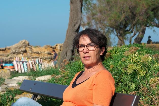 Porträt einer reifen frau mit brillen, sitzend auf einer bank