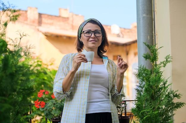 Porträt einer reifen hausfrau, weiblich mit einer tasse kaffee auf einem offenen balkon, der mit grünen pflanzen dekoriert ist