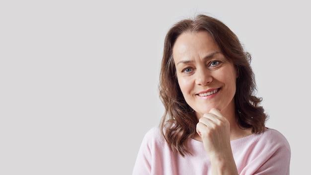 Porträt einer reifen, schönen frau in einem rosa pullover