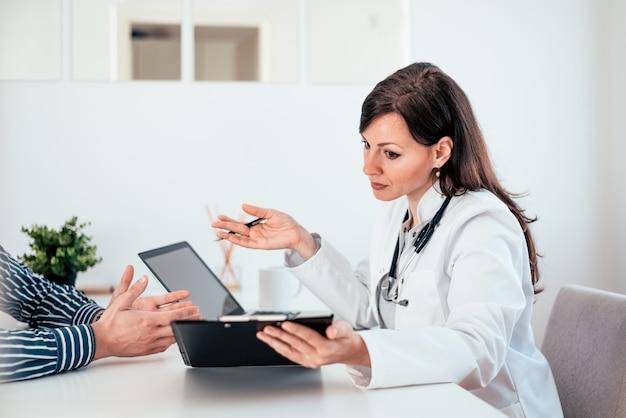 Porträt einer reizend ärztin, die mit einem patienten über testergebnisse spricht.