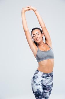 Porträt einer reizenden fitnessfrau, die hände lokalisiert auf einer weißen wand streckt