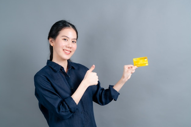 Porträt einer reizenden jungen asiatischen frau, die kreditkarte mit kopienraum zeigt