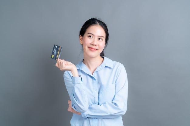 Porträt einer reizenden jungen asiatischen frau im blauen hemd, das kreditkarte mit kopienraum auf grauer wand zeigt