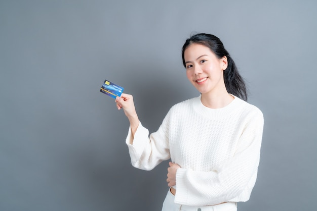 Porträt einer reizenden jungen asiatischen frau im pullover, der kreditkarte mit kopienraum auf grauer wand zeigt