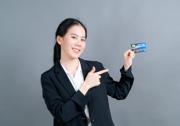 Porträt einer reizenden jungen asiatischen frau in offizierskleidung, die kreditkarte mit kopienraum auf grauer wand zeigt