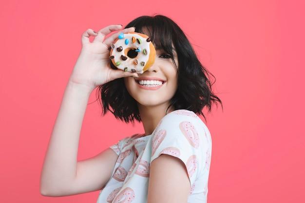 Porträt einer reizenden jungen kaukasierin des glamours gekleidet in einem hemd mit donuts, die durch einen donut schauen, der gegen einen rosa studiohintergrund lacht.