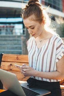Porträt einer reizenden rothaarigen frau mit sommersprossen, die ihr smartphone ernsthaft betrachten, während sie auf der bank sitzen und einen laptop auf ihren beinen halten.