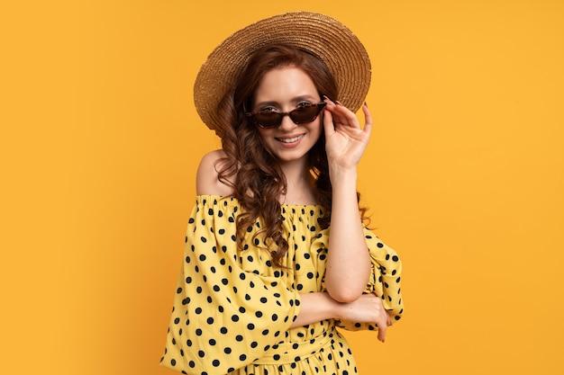 Porträt einer rothaarigen frau mit strohhut und stilvoller sonnenbrille, die im sommerkleid auf gelb posiert.