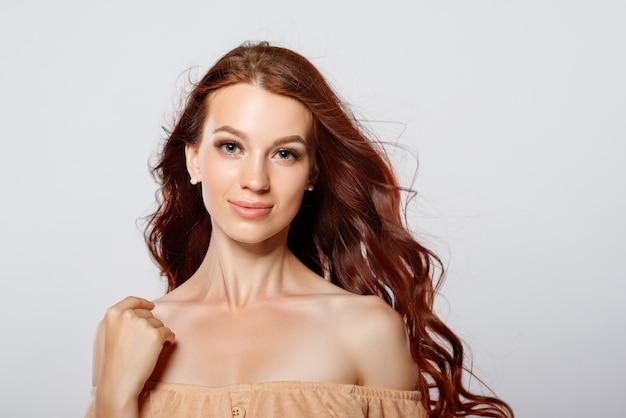 Porträt einer rothaarigen schönen jungen frau auf einem hellen hintergrund