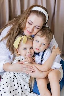 Porträt einer ruhigen, ausgeglichenen mutter umarmt sanft das familienkonzept ihrer kinder
