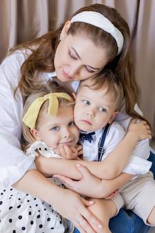 Porträt einer ruhigen, ausgeglichenen mutter umarmt sanft ihre kinder, glückliche kinder umarmen sich gegenseitig