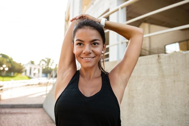 Porträt einer schlanken fitnessfrau, die ihre hände streckt