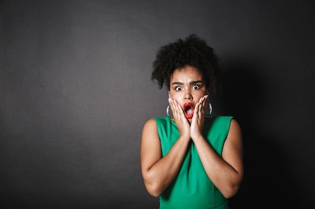 Porträt einer schockierten afroamerikanischen frau, die kleid trägt, das über schwarzer wand steht