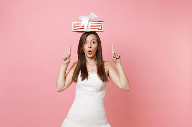Porträt einer schockierten aufgeregten frau im weißen kleid, die mit den zeigefingern auf die rote schachtel mit geschenk zeigt, das auf dem kopf vorhanden ist