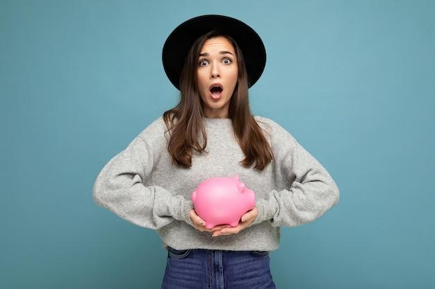 Porträt einer schockierten, erstaunten jungen, schönen brünetten frau, die einen stylischen grauen pullover und einen schwarzen hut trägt, einzeln auf blauem hintergrund mit leerem raum und mit rosafarbenem sparschwein. konzept der spardose.