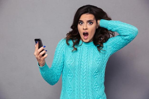 Porträt einer schockierten frau, die smartphone über grauer wand hält
