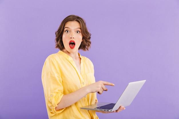 Porträt einer schockierten jungen frau, die auf laptop zeigt