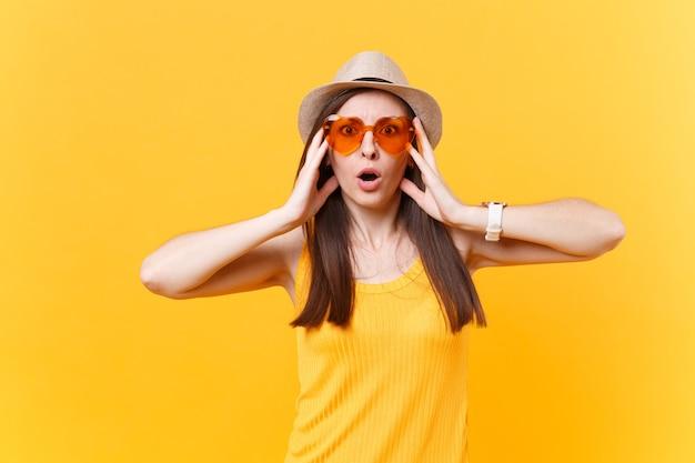 Porträt einer schockierten, lustigen, verrückten jungen frau mit strohsommerhut, orangefarbene gläser legen die hände auf das gesicht, kopieren raum einzeln auf gelbem hintergrund. menschen aufrichtige emotionen, lifestyle-konzept. werbefläche.
