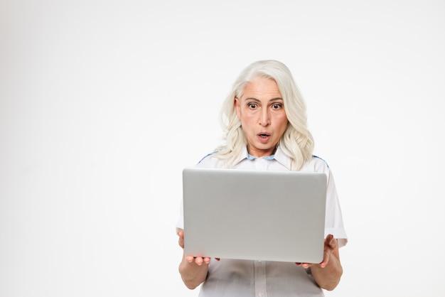 Porträt einer schockierten reifen frau, die laptop betrachtet