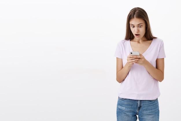 Porträt einer schockierten sprachlosen und verblüfften gut aussehenden jungen smartphone-besitzerin, die vor überraschung den kiefer fallen lässt und ungläubig und erstaunt auf den handybildschirm starrt, der auf schockierende nachrichten reagiert