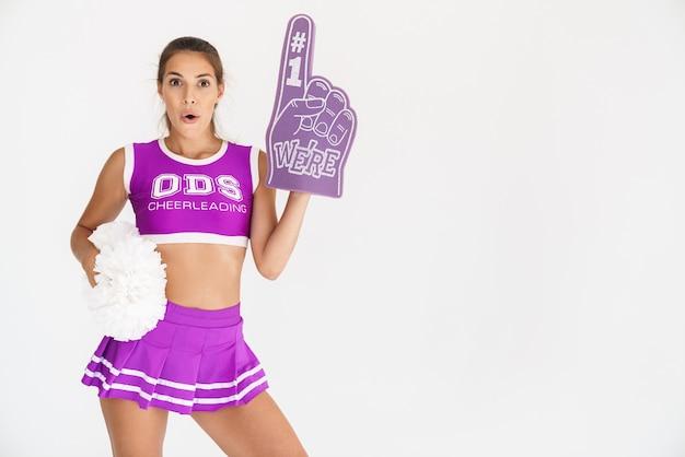 Porträt einer schockierten, überraschten cheerleaderin, die auf der weißen wand isoliert ist und die handschuhzeiger des ventilators nummer eins trägt.