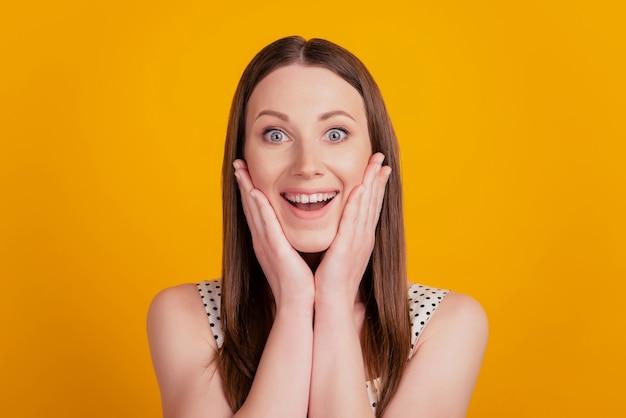 Porträt einer schockierten überraschten dame mit offenem mund und wangen auf gelbem hintergrund