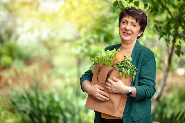 Porträt einer schönen 60-jährigen frau mit einer papiertüte in ihren händen mit gesunden produkten.