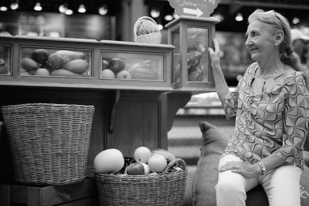 Porträt einer schönen älteren frau, die sich in der stadt bangkok in schwarz und weiß entspannt