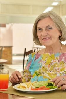 Porträt einer schönen älteren frau im café