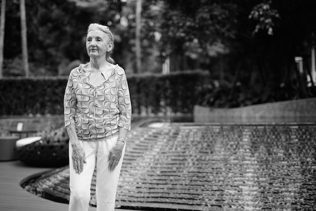 Porträt einer schönen älteren touristenfrau, die sich in der stadt bangkok in schwarz und weiß entspannt