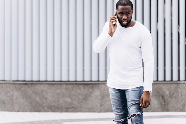 Porträt einer schönen afroamerikanischen mann mit lässigen kleidung in der modernen stadt sprechen am telefon