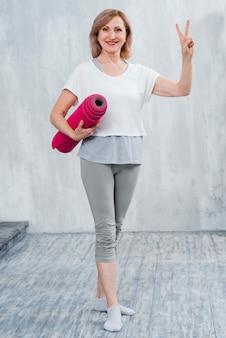 Porträt einer schönen alten frau mit der yogamatte, die zu hause siegeszeichen zeigt