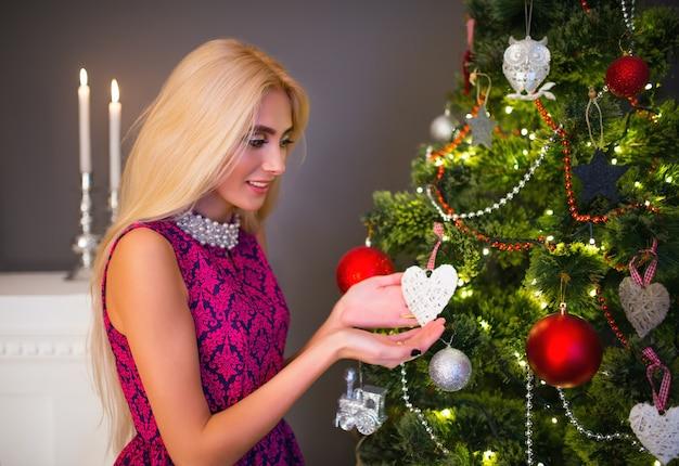 Porträt einer schönen anmutigen jungen blonden frau, die ein herz auf einem verschwommenen weihnachtsbaum und geschenken hält