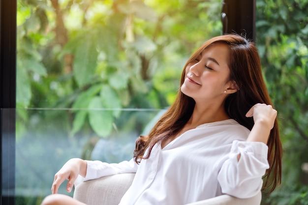 Porträt einer schönen asiatischen frau, die auf einem weißen sessel mit grüner natur sitzt