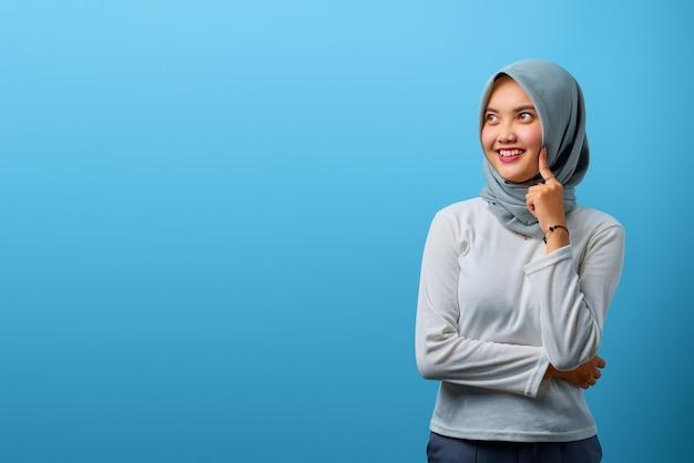 Porträt einer schönen asiatischen frau, die lächelt und beiseite schaut, während sie die wangen mit dem finger berührt
