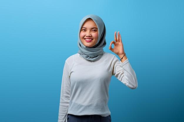 Porträt einer schönen asiatischen frau, die mit der hand auf blauem hintergrund ein okayzeichen tut