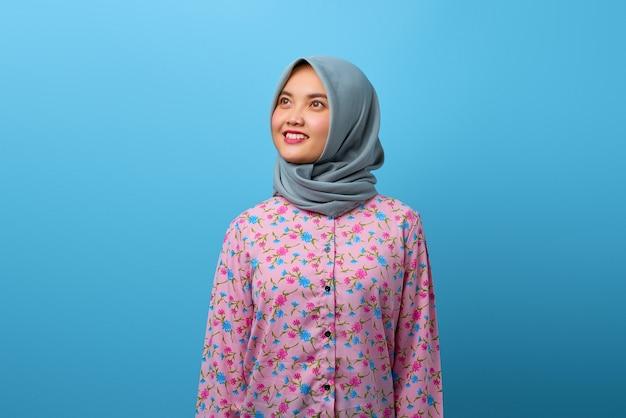 Porträt einer schönen asiatischen frau, die mit einem glücklichen lächeln im gesicht wegschaut
