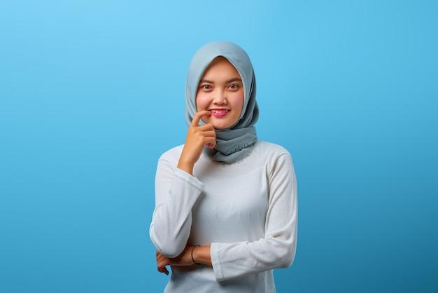 Porträt einer schönen asiatischen frau, die mit erhobener hand lächelt und die lippen mit dem finger berührt