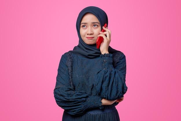 Porträt einer schönen asiatischen frau, die mit gelangweiltem ausdruck per smartphone spricht