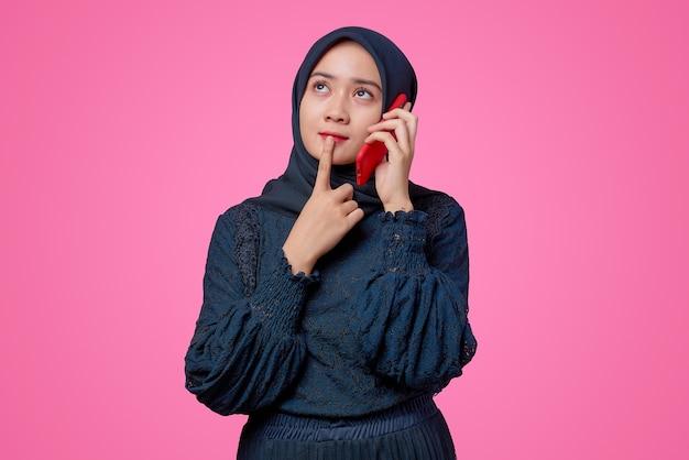 Porträt einer schönen asiatischen frau, die per smartphone mit denkendem ausdruck spricht