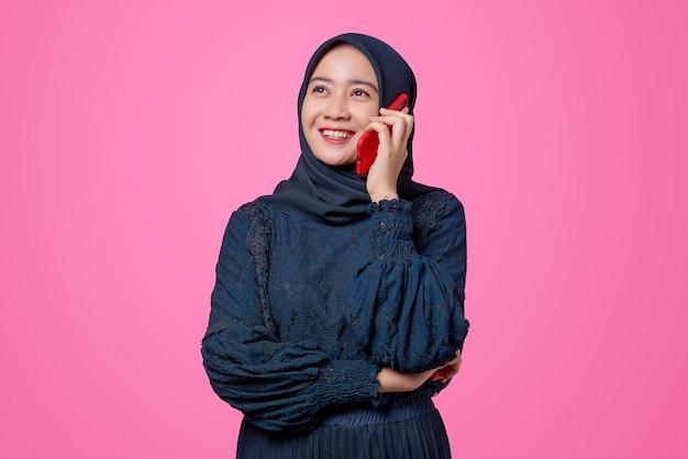Porträt einer schönen asiatischen frau, die per smartphone mit glücksausdruck spricht