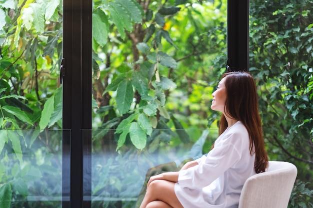 Porträt einer schönen asiatischen frau, die sitzt und eine grüne natur außerhalb des fensters betrachtet