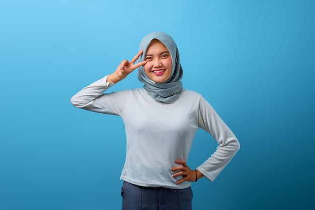 Porträt einer schönen asiatischen frau, die über dem auge ein friedenszeichen lächelt und zeigt
