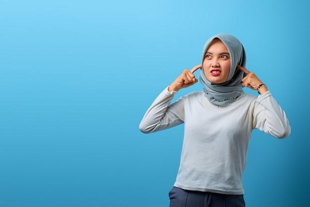 Porträt einer schönen asiatischen frau, die wütend ist und ihre ohren mit dem finger bedeckt