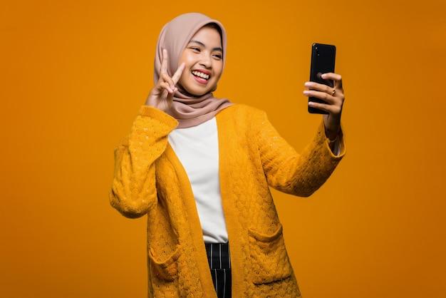 Porträt einer schönen asiatischen frau fröhlich mit handy