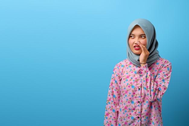 Porträt einer schönen asiatischen frau hält die hand in der nähe des mundes und flüstert geheimnis auf blauem hintergrund